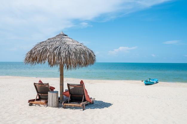 トロピカルビーチのパラソルの下で2つの椅子
