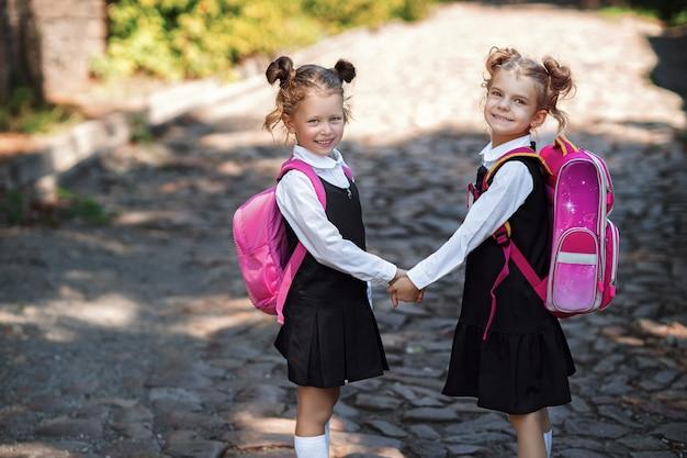学校のバックパックを着て2つの笑顔の学生の女の子。小学校の外の幸せな白人少女の肖像画。カメラを見て笑顔の女子高生