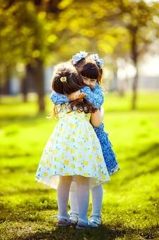 屋外で楽しんでいるかわいい女の子。 2人のかわいい女の子が緑の草の上に立ってハグします。