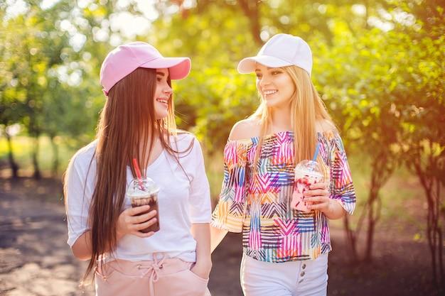 飲み物を持つトレンディな2人の女性