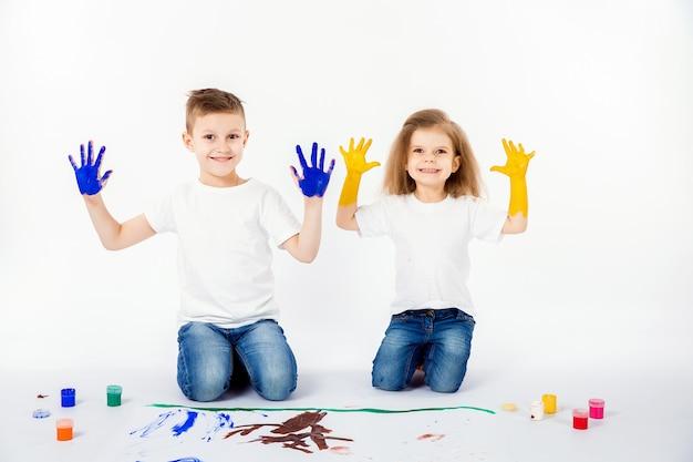 2人のかわいい子供の友人の男の子と女の子が絵の具で絵を描いています