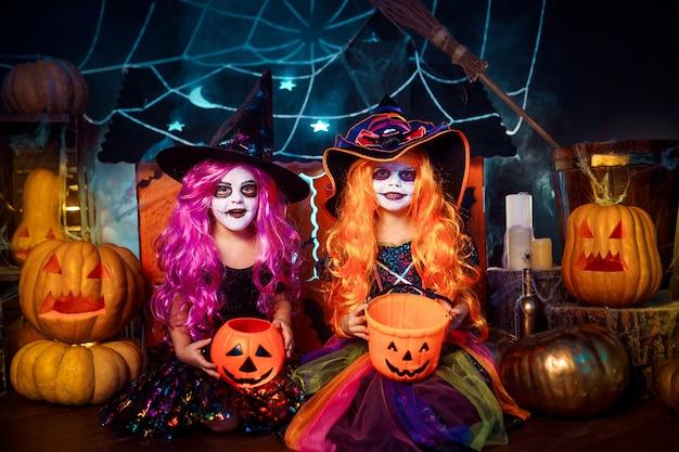 2人のかわいい面白い姉妹が休日を祝います。ハロウィーンの準備ができてカーニバル衣装で陽気な子供たち。