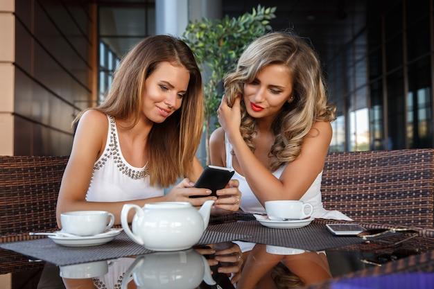 カフェに座っている2つのガールフレンド