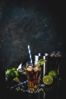 キューバリブレ、ロングアイランドまたはアイスティーカクテル、強いアルコール、コーラ、ライム、氷、2枚のガラス、暗い表面のコピースペース