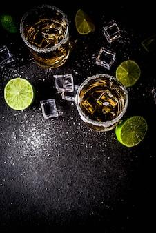 アイスキューブ、塩、ライムの暗いテーブルの上の2つのテキーラショットグラス