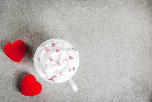 ロマンチックな、バレンタインの日。コーヒーまたはホットチョコレートのカップ、ホイップクリームと甘いハート、2つの豪華な赤いハート、トップビュー