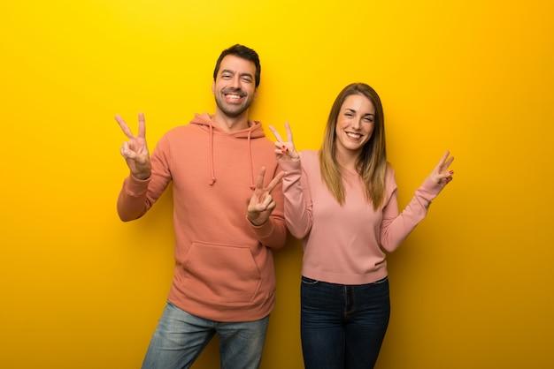 バレンタインの日に笑みを浮かべて、両手で勝利のサインを示す黄色の背景に2人のグループ
