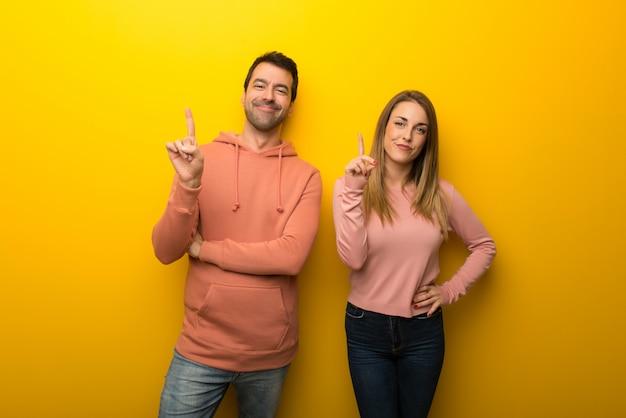 バレンタインの日に黄色の背景に2人のグループを表示し、最高のサインで指を持ち上げる