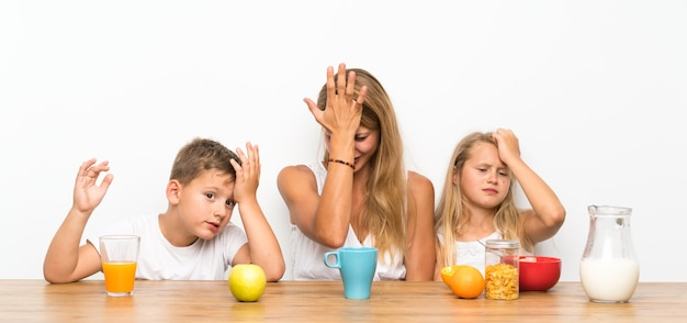 朝食と疑問を持っている2人の子供を持つ母