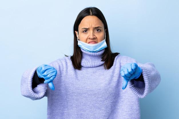 2つの手で親指を示す青い壁の上のマスクと手袋で保護する若いブルネット混血女性
