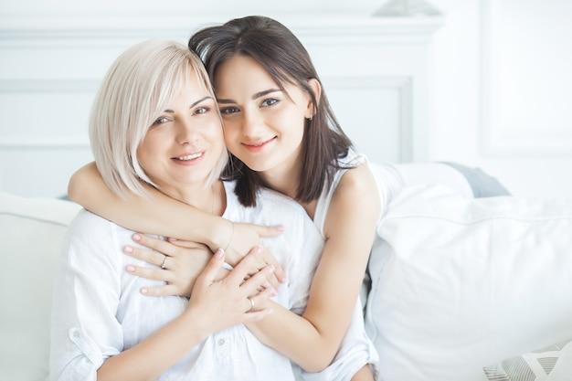 Портрет крупного плана 2 красивых женщин мама и дочь. средняя взрослая мать обнимая ее взрослую дочь внутри помещения. счастливые улыбающиеся женщины обнимаются.