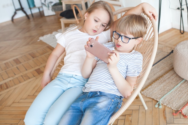 スマートフォンで遊ぶ2人の子供。男の子と女の子が自宅で携帯電話を見ています。屋内デジタル子供。