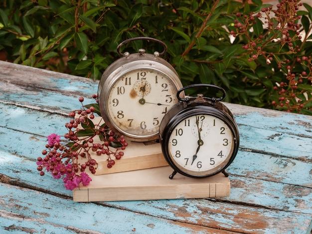時間の概念。 2つの古い時計と素朴な木製のテーブル上の古い本