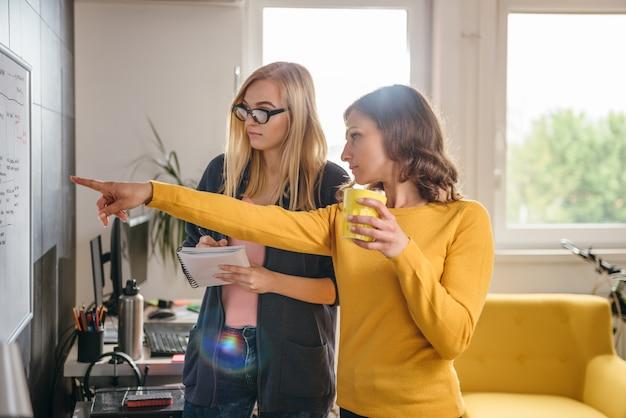 ホワイトボードの前で議論する2つのビジネス女性