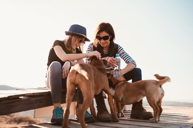 母と娘が屋外で2匹の犬を抱きしめる