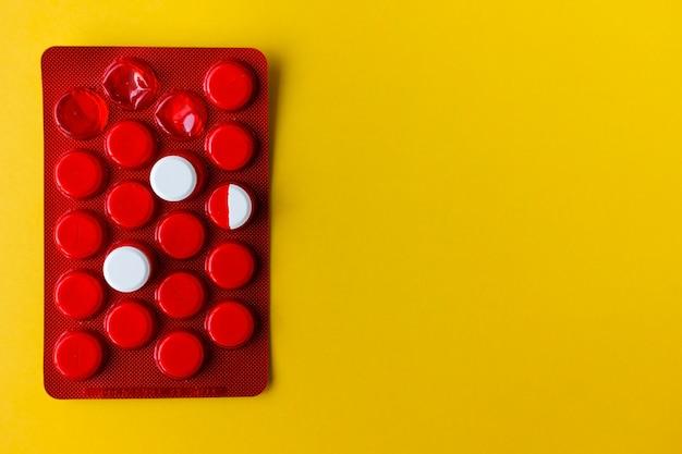 2つの白い丸薬と半分はコピースペースと赤いパッケージにあります。