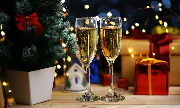 クリスマスツリーのそばのシャンパンの2つのガラス