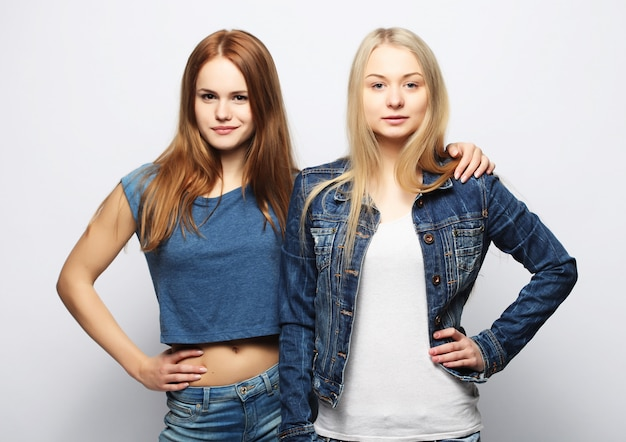 一緒に立っていると楽しい2人の若いガールフレンド。