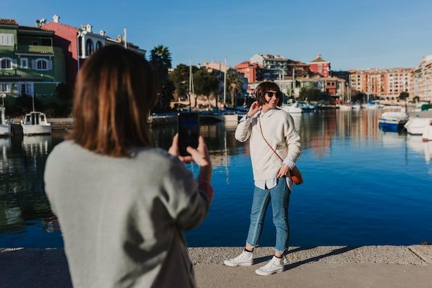 携帯電話で写真を撮る通りの2人の友人。晴れた日のポートの背景。屋外のライフスタイル。友情の概念