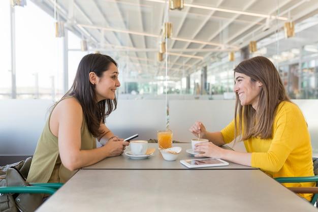 レストランで朝食を持っている2人の美しい女性。彼らは笑って、携帯電話で情報を検索しています。屋内のライフスタイルと友情の概念