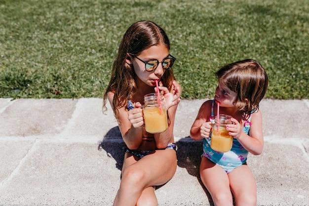 健康的なオレンジジュースを飲むと、屋外で楽しんでプールで2人の美しい姉妹の子供。夏とライフスタイルのコンセプト