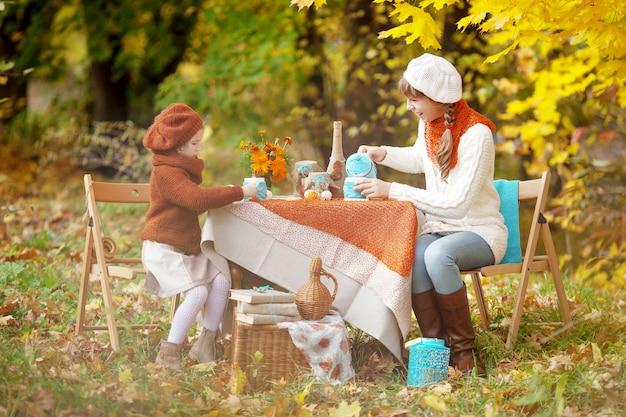 秋の公園でピクニックに2人のかわいい姉妹。秋の庭でお茶会をしている愛らしい少女。季節ごと。