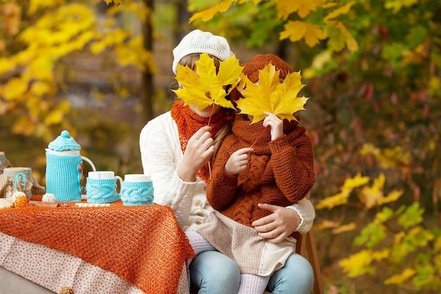 秋の公園でピクニックに2人のかわいい姉妹。秋の庭でお茶会をしている愛らしい少女。黄色の葉で撚る女の子。