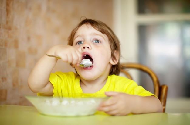 2歳の子供自身が乳製品を食べる