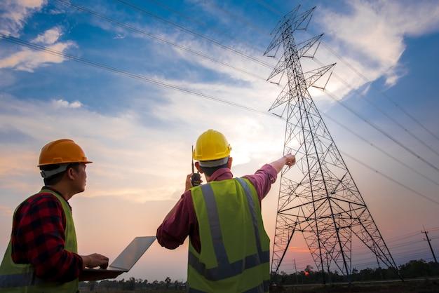 高圧電極での計画作業を確認するために、発電所に立っているコンピューターを使用して電気作業をチェックしている2人の電気技師の写真。