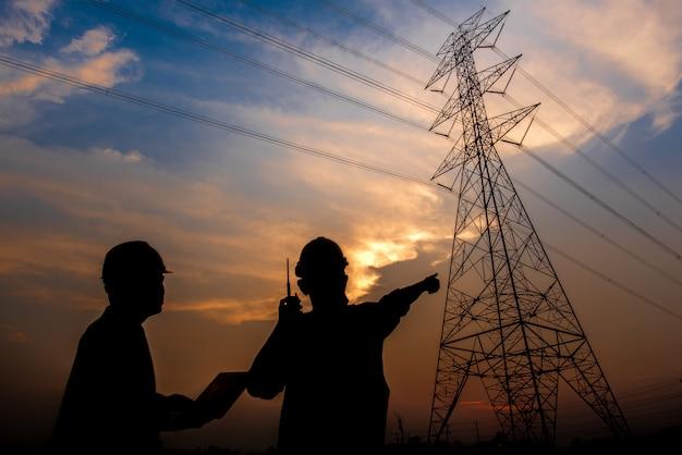 高電圧電極で電気を生成することによって計画作業を確認するために発電所に立っている2人の電気技師のシルエット。