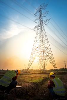 高電圧電極での計画作業を確認するために発電所で写真を撮ることによって電気作業をチェックしている2人の電気技師の写真。