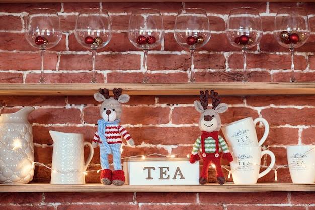 子供のおもちゃ。植木鉢近くに立っている縞模様のセーター、スカーフ、蝶ネクタイの2つのスタイリッシュなアミグルミ鹿。のクリスマスライト。無料のコピースペース。