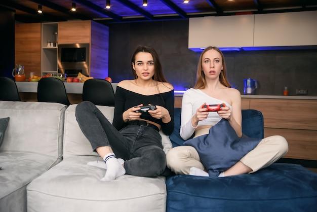 隔離中に自宅でコンピュータゲームをすることに情熱を傾ける2人のガールフレンド。世界パンデミックの家の隔離。余暇を過ごす時間を楽しんでください。