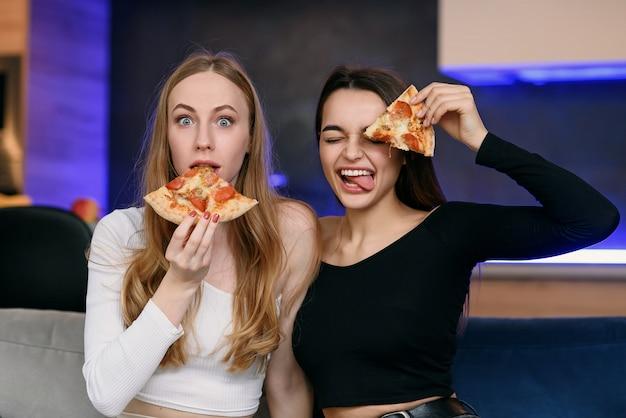 2人の女性が家で楽しんで、ピザの箱を開け、食品配達、ホームパーティー