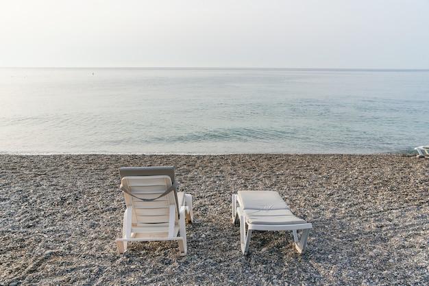 日の出の海のビーチに2つのプラスチック製のサンベッド。夏休みのコンセプトです。背面図。