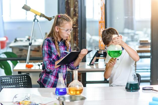 子供たちは実験の結果をノートに記録します。ビーカーとドライアイスで緑色の液体で実験を行う保護メガネの2人の若い巧妙な白人生徒。