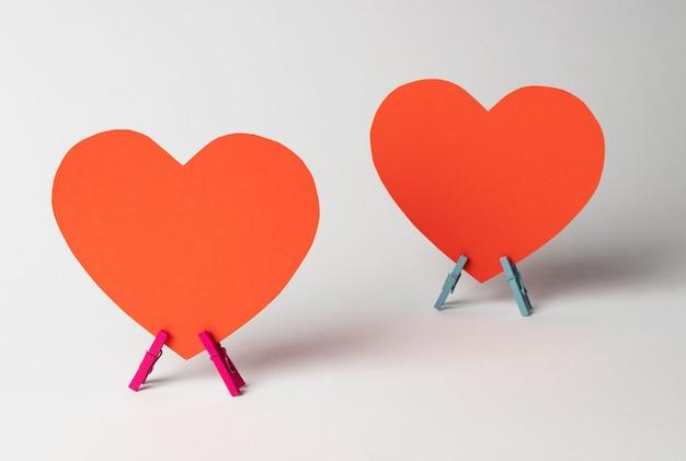 白い背景の上の木製洗濯はさみの上に2つの紙の心が立っています。最小限の愛の概念。