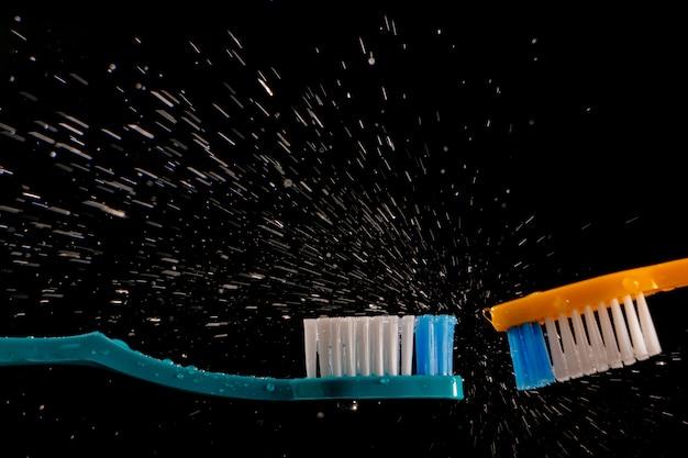 黒の背景にはねかける水で2つの歯ブラシ。