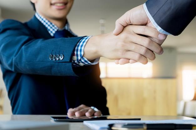 オフィス、成功、対処、挨拶とパートナーのコンセプトで会議中に2人の自信を持ったビジネスマンが握手