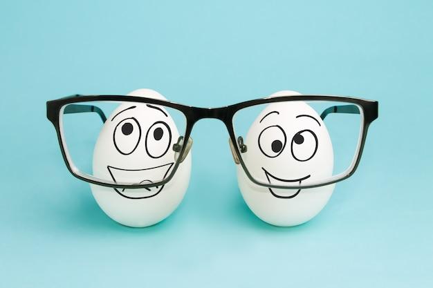 2つの面白い卵は眼鏡のレンズを通して見ます。視力矯正