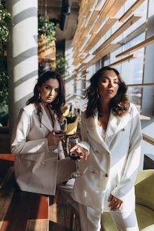 2人のスタイリッシュでセクシーな魅力的なエレガントな女性は、ワインを飲みながらレストランで白いスーツを着ます。