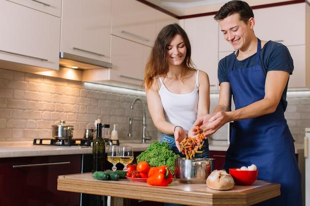 台所で美しいカップル。食べ物を準備する2人家族。おいしいパスタを作る