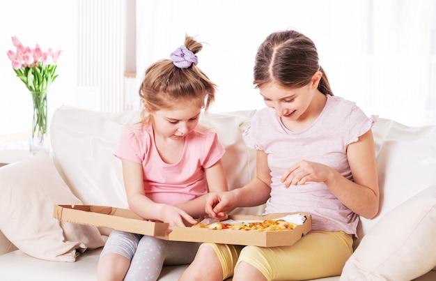 2人の女の子がピザを食べている