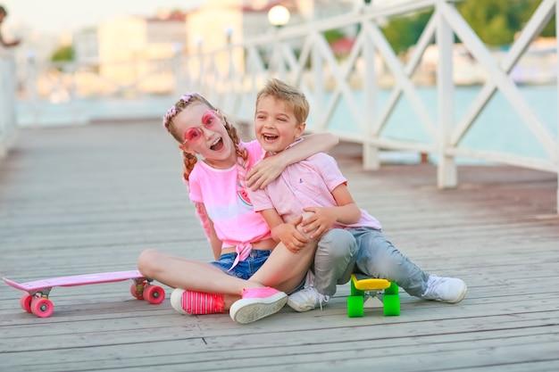 彼らの隣の床に座っている2人の友人の男の子と女の子の子供たちは子供のスケートボード