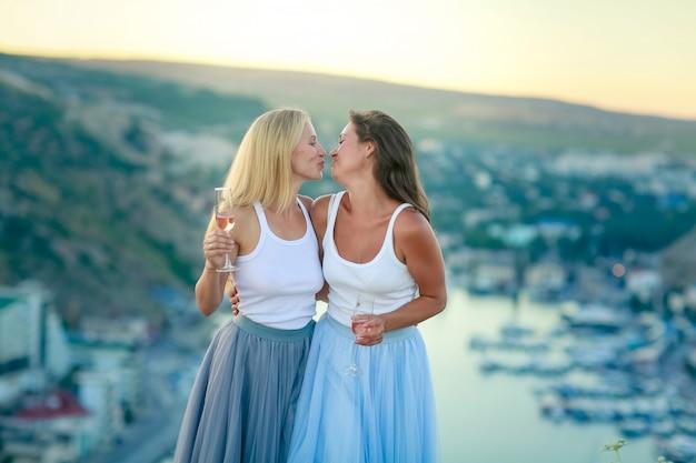 ドレスを着た2人の大人の姉妹女性が眼鏡を手に山の頂上に立つ