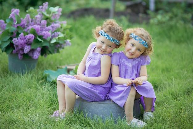 春の緑の自然公園で紫の衣装を着た2人の双子の姉妹
