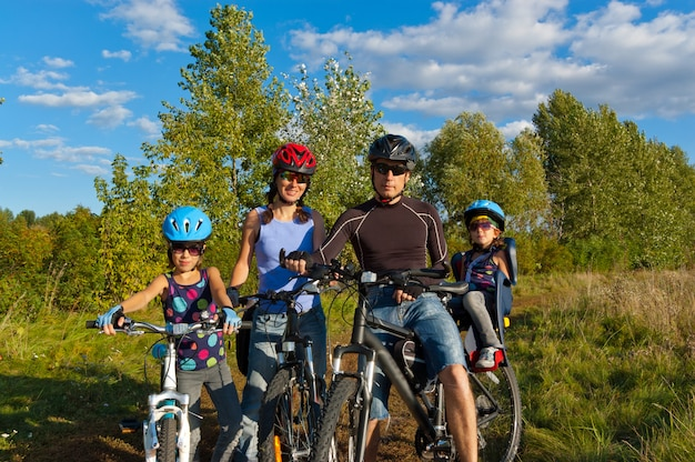 家族の屋外サイクリング。自転車で2人の子供を持つ幸せな親
