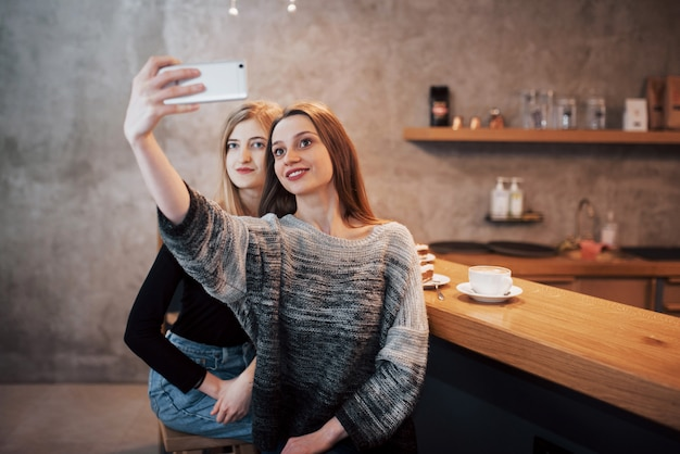 2人の女の子がカフェで笑顔とスマートフォンを使用しています。