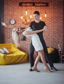 ラテン音楽を踊る若いカップル:バチャータ、メレンゲ、サルサ。レンガの壁とカフェで2つの優雅なポーズ