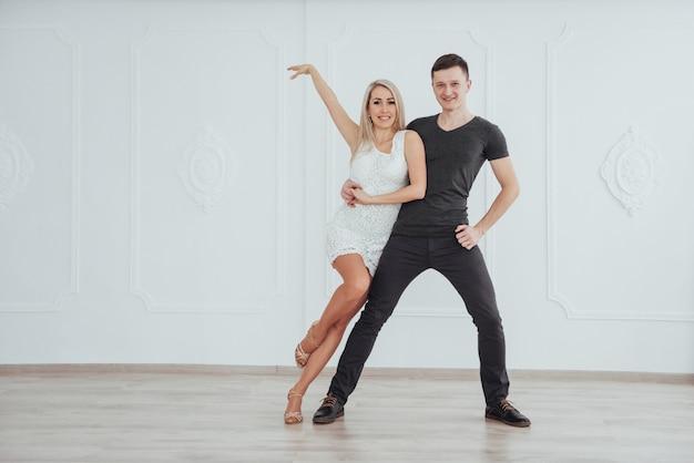 ラテン音楽を踊る若いカップル:バチャータ、メレンゲ、サルサ。白い部屋に2つの優雅さのポーズ